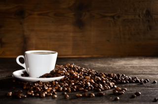 Cup-of-coffee-with-a-pile-of-coffee-beans_1112-438