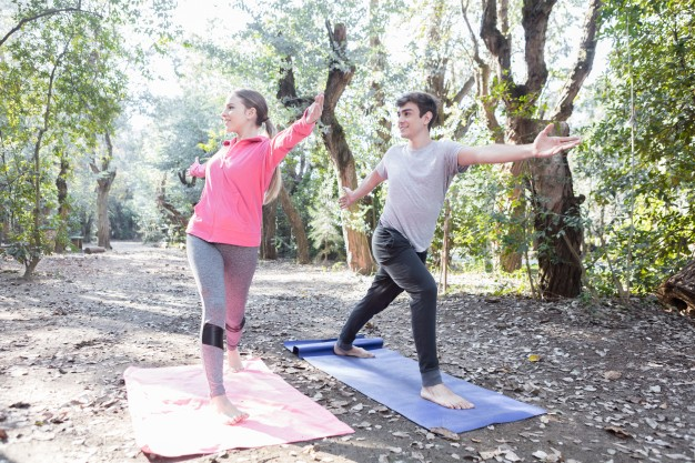 Young-couple-stretching-arms-and-legs-during-a-yoga-class_23-2147562260
